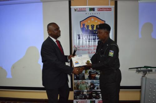 An officer receiving certificate from Mister Motivator