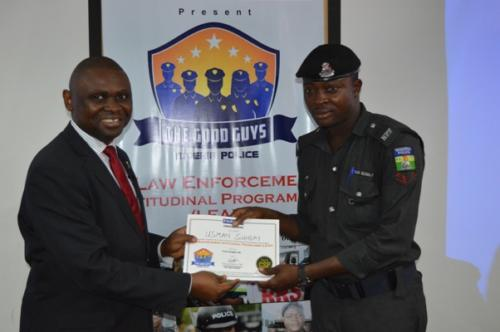 Mister motivator presenting certificate to an officer