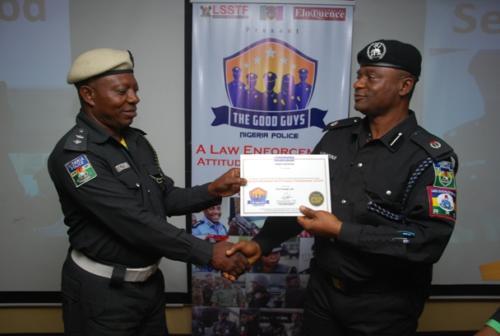 An officer receiving certificate from DCP Disu
