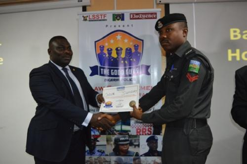 Degbola Lewis presenting certificate to one of the officers